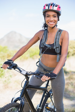 Fit woman going for bike ride smiling at camera on a sunny day in the countryside photo