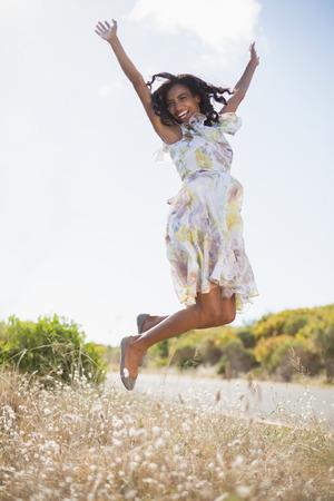 Gelukkige mooie vrouw springen in gebloemde jurk op een zonnige dag op het platteland Stockfoto
