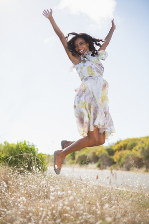 Happy pretty woman jumping up in floral dress on a sunny day in the countryside