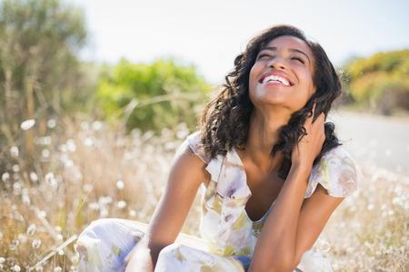 freiheit: Glückliche hübsche Frau sitzt auf dem Rasen im Blumenkleid an einem sonnigen Tag in der Natur