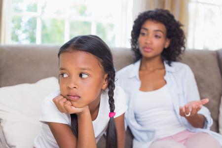 irrespeto: Madre bonita que se sienta en el sofá después de una discusión con su hija en su casa en la sala de estar