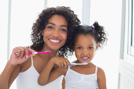 homely: Pretty mother with her daughter brushing their teeth at home in the bathroom Stock Photo