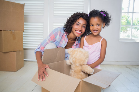 Cute daughter unpacking her teddy bear with mother in their new home photo
