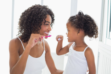 smile teeth: Pretty mother with her daughter brushing their teeth at home in the bathroom Stock Photo