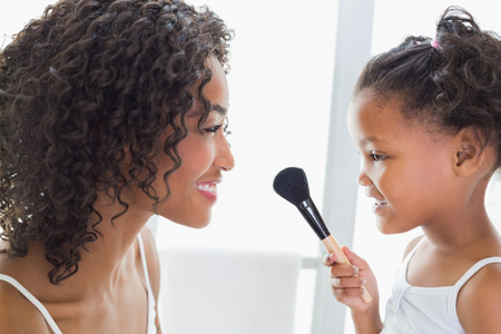 Pretty mother teaching her daughter about makeup at home in the bathroom photo