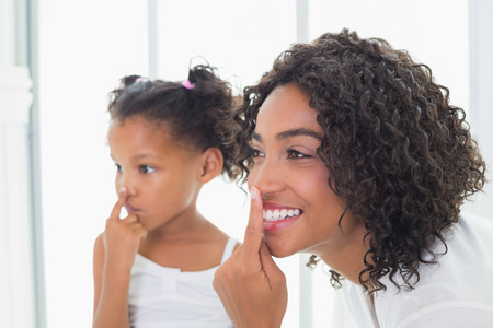 rubbing noses: Pretty mother putting face cream on with her daughter at home in the bathroom