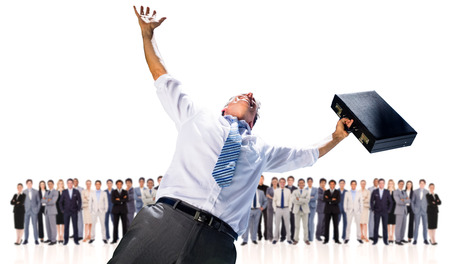 Composite image of businessman holding briefcase and cheering against row of business people photo