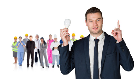 boiler suit: Composite image of businessman holding light bulb and pointing against group of workers