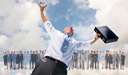 Businessman holding briefcase and cheering against blue sky with white clouds Stock Photo