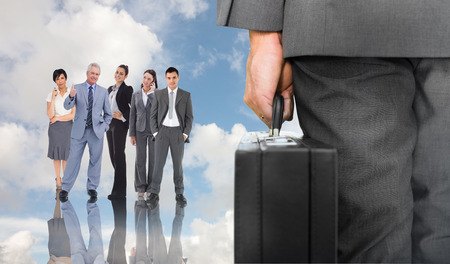 Businessman holding briefcase against blue sky with white clouds and business people photo