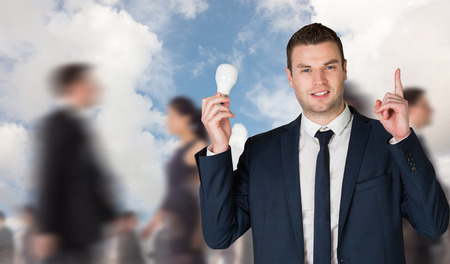 Businessman holding light bulb and pointing against blue sky with white clouds photo