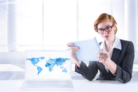 Redhead businesswoman using her tablet pc with laptop showing graphic photo