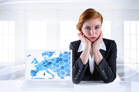Redhead businesswoman looking unhappy  with laptop showing graphic photo