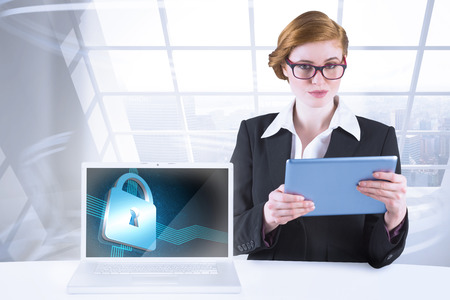 Redhead businesswoman using her tablet pc  with laptop showing shiny lock on black background photo