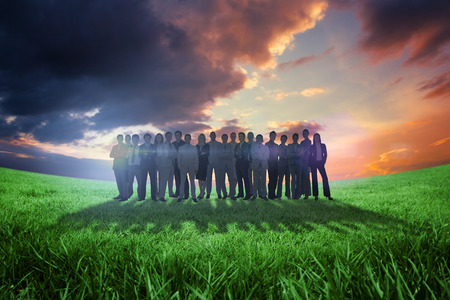 Business people standing up against green field under orange sky photo