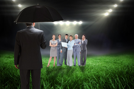 Mature businessman holding an umbrella against football pitch with bright lights photo