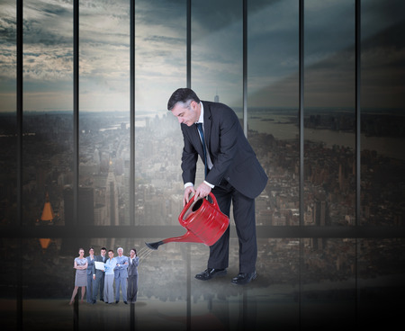 Mature businessman watering tiny business team against room with large window looking on city photo