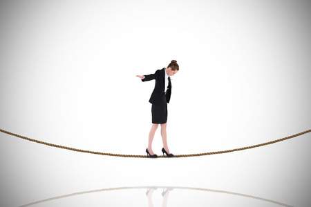balancing act: Businesswoman performing a balancing act on tightrope against white background with vignette