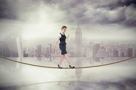 tight focus: Businesswoman doing a balancing act on tightrope against room with large window looking on city Stock Photo