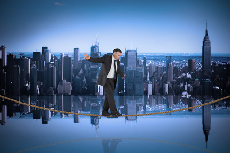Mature businessman doing a balancing act on tightrope against mirror image of city skyline photo