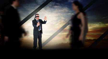 Mature businessman in a blindfold against room with large window looking on landscape