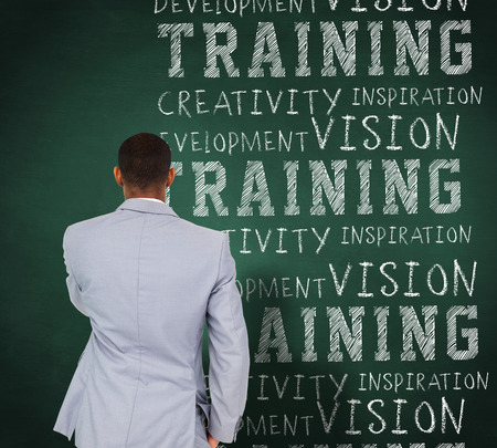 buzzwords: Thinking businessman against green chalkboard with business buzzwords