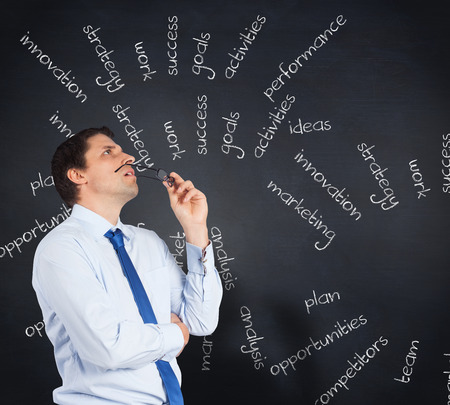 buzzwords: Thinking businessman biting glasses against blackboard with business buzzwords Stock Photo