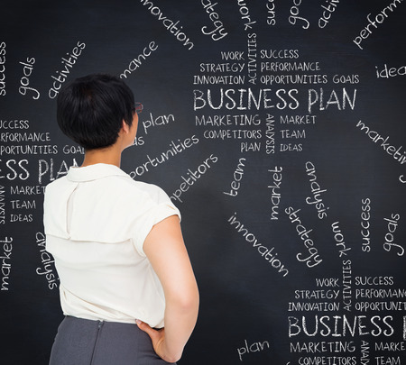 buzzwords: Thoughtful businesswoman against blackboard with business buzzwords