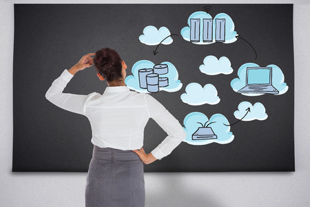 Businesswoman scratching her head against black chalkboard with business technology doodle photo