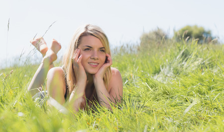 Pretty blonde in sundress lying on grass on a sunny day in the countryside photo