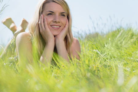 Pretty blonde in sundress lying on grass smiling on a sunny day in the countryside photo