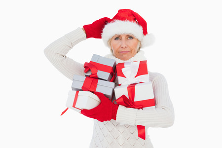 Festive woman scratching head and holding gifts on white background photo