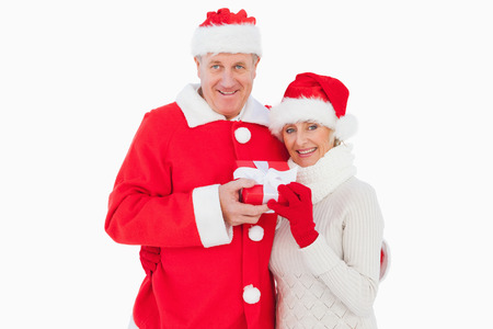 Festive couple smiling and holding gift on white background photo