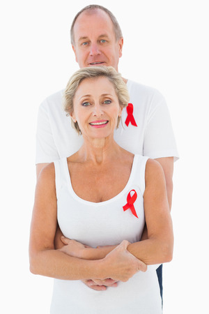 Mature couple supporting aids awareness together on white background photo