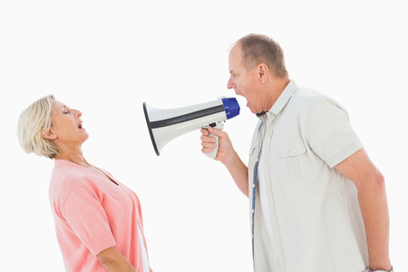 Man shouting at his partner through megaphone on white background photo