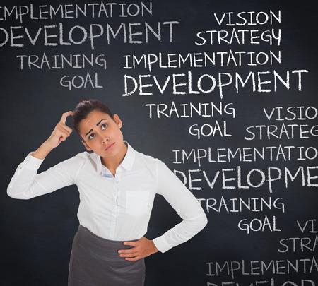 buzzwords: Worried businesswoman against blackboard with business buzzwords
