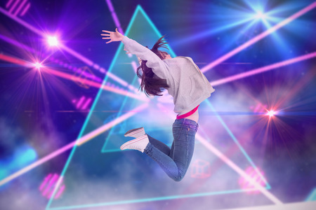 laser lights: Cheerful young woman jumping against digitally generated laser lights background