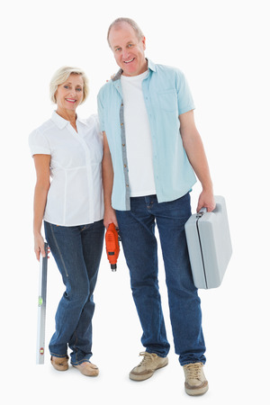 Happy older couple holding diy tools on white background photo