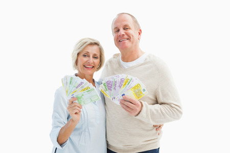 Happy mature couple smiling at camera showing money on white background photo
