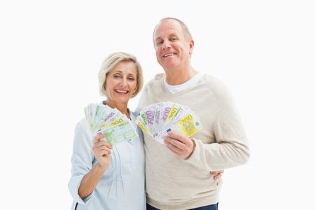 Happy mature couple smiling at camera showing money on white background photo