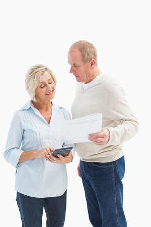 Mature couple working out their bills on white background photo