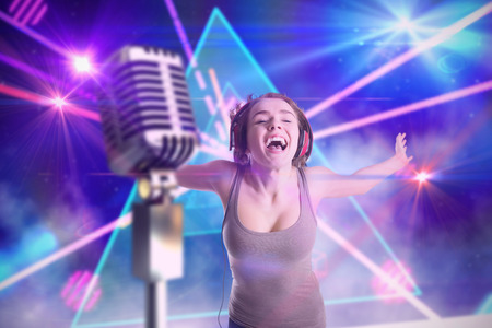 laser lights: Pretty girl listening to music against digitally generated laser lights background Stock Photo