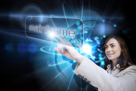 Businesswoman pointing to word mainframe against shiny sphere on black background photo