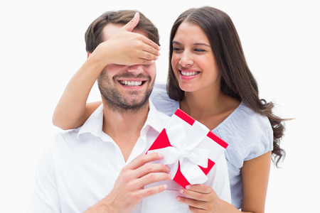 Pretty brunette surprising boyfriend with a gift on white background
