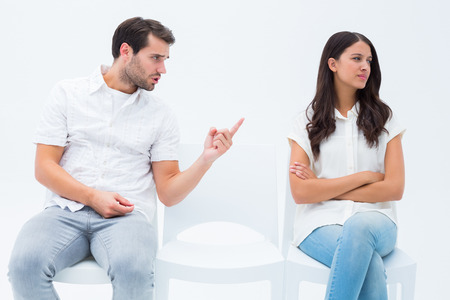Man pleading with angry girlfriend on white background Stock Photo