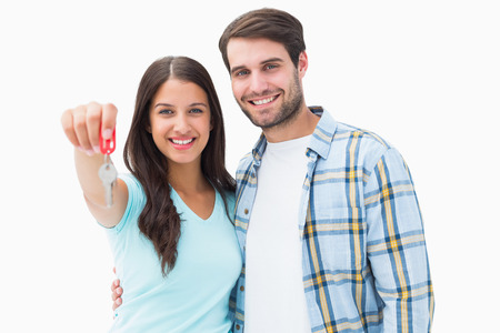 Happy young couple showing new house key on white background photo