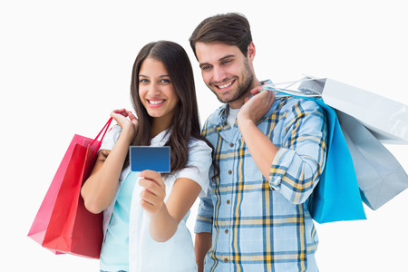 Attractive young couple with shopping bags and credit card on white background photo