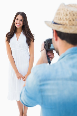 Hipster taking a photo of pretty girlfriend on white background photo