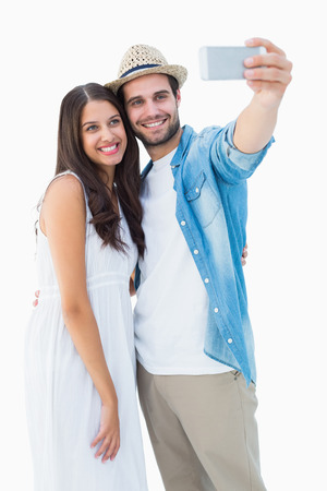 Happy hipster couple taking a selfie on white background Stock Photo