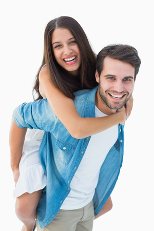Happy hipster giving his girlfriend a piggy back on white background photo